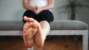 Kvinnan visar och trycker på hennes fot, ben och anklar arkivfilmer
