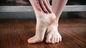 Kvinnan visar och trycker på hennes fot, ben och anklar stock video