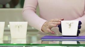 Kvinnan visar olikt smyckengods på shoppa arkivbild