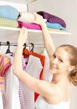 Kvinnan väljer kläder i garderobgarderoben hemma Arkivbild