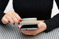 Kvinnan välter läst liten text på mobiltelefonen utan förstorande gl Royaltyfri Fotografi