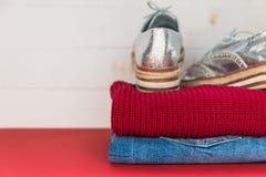 Kvinnanedgång-/vinterkläder vek på röd bakgrund Jeans gult stuckit förkläde, silverlägenhetskor arkivfoton
