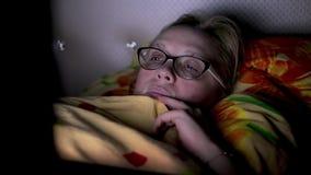 Kvinnans framsida exponeras av en bärbar datorbildskärm Flicka som ligger på sängen under filten och blickar på skärmen stock video