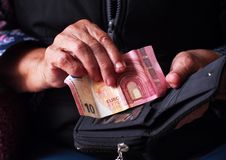 Kvinnans händer rymmer några euromynt Pension, armod, sociala problem och temat av gamlingen royaltyfri fotografi