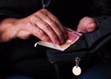 Kvinnans händer rymmer några euromynt Pension, armod, sociala problem och temat av gamlingen arkivbild