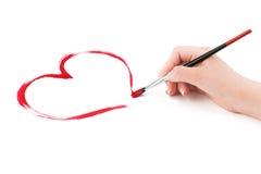 Kvinnans hand drar en hjärta. arkivfoto