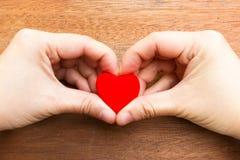Kvinnans hand gör en hjärta att forma och rymma en röd hjärtaform Arkivbilder