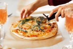 Kvinnans hand med en kniv klippte pizza på den vita bakgrundsnärbilden fotografering för bildbyråer