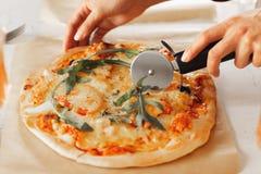 Kvinnans hand med en kniv klippte pizza på den vita bakgrundsnärbilden royaltyfria bilder