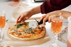 Kvinnans hand med en kniv klippte pizza p? den vita bakgrundsn?rbilden royaltyfria bilder