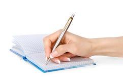 Kvinnans hand med en penna skriver i en isolerad anteckningsbok Arkivbild