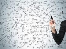 Kvinnans hand pekar ut de invecklade matematikberäkningarna Arkivbild