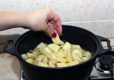 Kvinnans hand satte tärning för en potatis in i den svarta metallkastrullen Arkivfoto