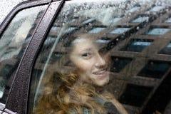 Kvinnans leende ljusnar den regniga dagen Royaltyfri Foto