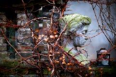 Kvinnans skulptur i trädgård Arkivbild