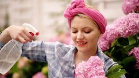 kvinnaomsorg av blommor i trädgård lycklig kvinnaträdgårdsmästare med blommor Omsorg och bevattna för blomma jorder och gödningsm lager videofilmer