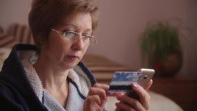 Kvinnaonline-bankrörelsen genom att använda smartphonen som direktanslutet shoppar med hemmastadd livsstil för kreditkort stock video