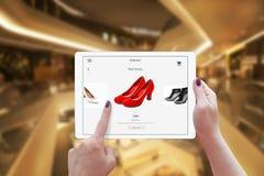 Kvinnaonline-shopping med minnestavlan Den hållande apparaten och väljer röda skor Arkivfoto