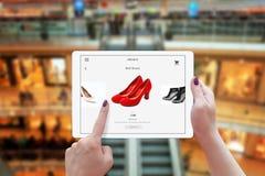 Kvinnaonline-shopping med minnestavlan Den hållande apparaten och väljer röda skor Royaltyfria Bilder