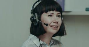 Kvinnaoperatören som startar arbetet, får hennes hörlurar med mikrofon i ett kontor stock video