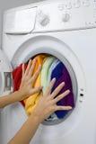 Kvinnapäfyllningstvätteri i tvagningmaskinen Royaltyfria Bilder