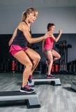 Kvinnapar som utbildar över steppers i aerobiskt royaltyfri bild