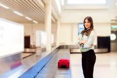 Kvinnapassagerare i 20-tal som väntar hennes bagage på transportbandet Royaltyfri Foto