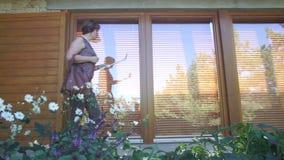 Kvinnapasserande nära höga fönster stock video