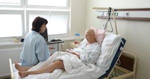 Kvinnapatient med cancer i sjukhus med vännen lager videofilmer