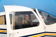 Kvinnapilot i flygplanet Arkivbild