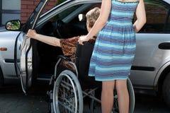 Kvinnaportionhandikappade personer får in i bilen Royaltyfria Bilder