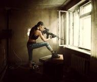 Kvinnaprickskytt och soldat som siktar geväret på fönstret royaltyfri bild