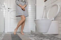 Kvinnaproblem som rymmer hennes händer i toalett Fotografering för Bildbyråer