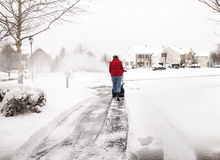 Kvinnaröjningkörbana med en snowblower Royaltyfria Bilder