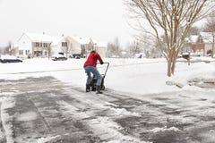 Kvinnaröjningkörbana med en snowblower Arkivbild