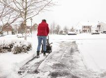 Kvinnaröjningkörbana med en snowblower Arkivfoto