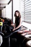 Kvinnaracerbilsförare i läderdräkten som rymmer en hjälm arkivfoto