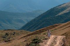 Kvinnaresande i bergen som går framåt till höjderna Arkivfoton