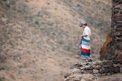 Kvinnaresande i bergen som går framåt till höjderna Arkivbild