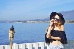 Kvinnaresande som talar på telefonen, gulligt flickaleende, på bakgrund av havet/havet Begreppet av anslutning Royaltyfri Bild