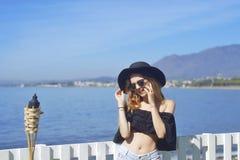 Kvinnaresande som talar på telefonen, gulligt flickaleende, på bakgrund av havet/havet Begreppet av anslutning Royaltyfri Foto