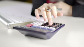 Kvinnarevisor som i regeringsställning beräknar och tar anmärkningar på det vita skrivbordet lager videofilmer