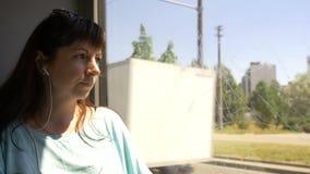 Kvinnaridning på bussen som ut ser fönstret och lyssnar till musik stock video