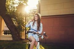 Kvinnaridning på cykeln arkivbild