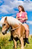 Kvinnaridning på häst i äng Arkivfoto