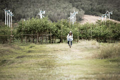 Kvinnaridningcykel i fält med vindturbinen i bakgrund Royaltyfri Bild