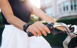Kvinnaridningcykel med en smartwatch royaltyfri fotografi