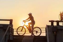 Kvinnaridningcykel som övar i solnedgångstad royaltyfria bilder
