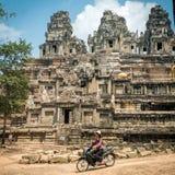 Kvinnaridningmoped framme av den gamla templet på det Angkor Wat komplexet Fotografering för Bildbyråer