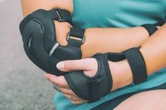 Kvinnarollerskater med armbågebeskyddandeblock på henne hand arkivbild
